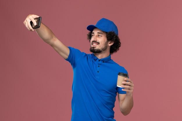 Vue avant du courrier masculin en uniforme bleu et capuchon avec tasse de café de livraison sur ses mains en prenant une photo sur un mur rose