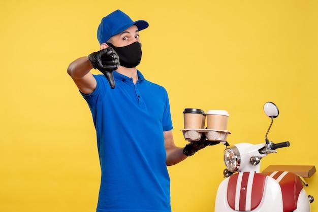 Vue avant du courrier masculin en uniforme bleu tenant le café sur le service d'emploi de couleur uniforme jaune covid- livraison de travail pandémique