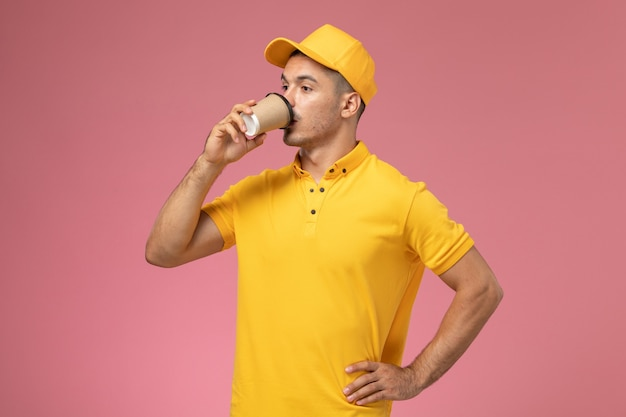 Vue avant du courrier masculin en uniforme jaune, boire du café sur le fond rose