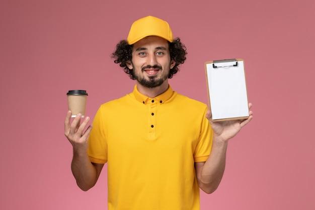 Vue avant du courrier masculin en uniforme jaune et cape tenant la tasse de café de livraison et le bloc-notes sur le mur rose