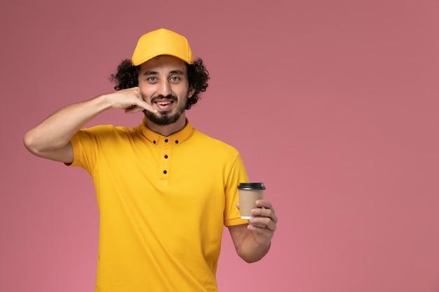 Vue avant du courrier masculin en uniforme jaune et cape tenant la tasse de café de livraison sur le mur rose clair