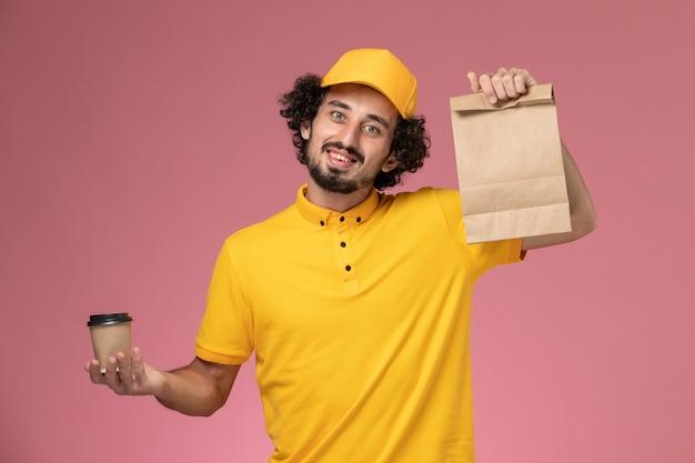 Vue avant du courrier masculin en uniforme jaune et cape tenant la tasse de café de livraison et le paquet de nourriture sur l'uniforme de bureau rose entreprise de services d'emploi mâle