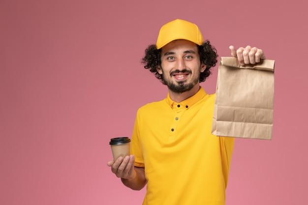Vue avant du courrier masculin en uniforme jaune et cape tenant la tasse de café de livraison et le paquet de nourriture sur l'uniforme de bureau rose travailleur de l'entreprise de service d'emploi mâle