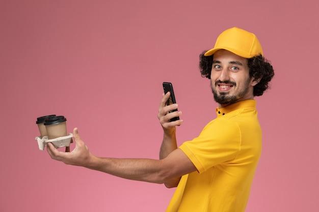 Vue avant du courrier masculin en uniforme jaune et cape tenant des tasses de café de livraison marron prenant photo sur mur rose