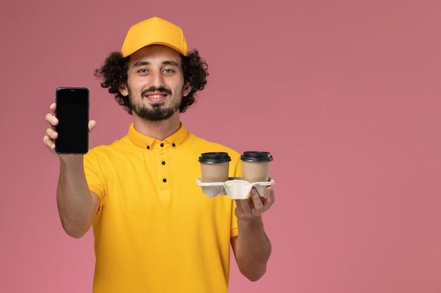 Vue avant du courrier masculin en uniforme jaune et cape tenant des tasses de café de livraison marron et téléphone sur le mur rose