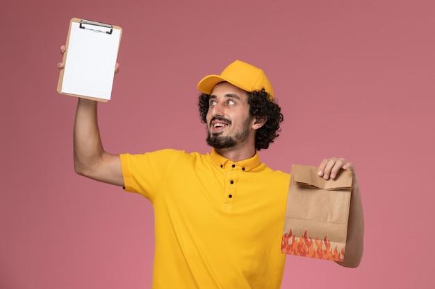 Vue avant du courrier masculin en uniforme jaune tenant le paquet de nourriture et le bloc-notes sur le mur rose