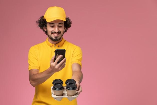 Vue avant du courrier masculin en uniforme jaune tenant des tasses de café de livraison marron en prenant une photo d'eux sur le mur rose