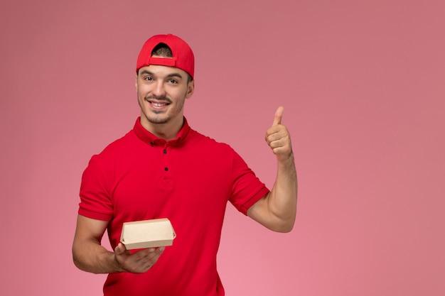 Vue avant du courrier masculin en uniforme rouge et cap tenant peu de colis de livraison sur le mur rose