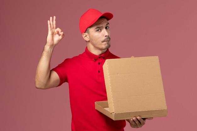 Vue avant du courrier masculin en uniforme rouge et cape tenant la boîte de nourriture l'ouvrant sur le travail de travailleur mural rose clair