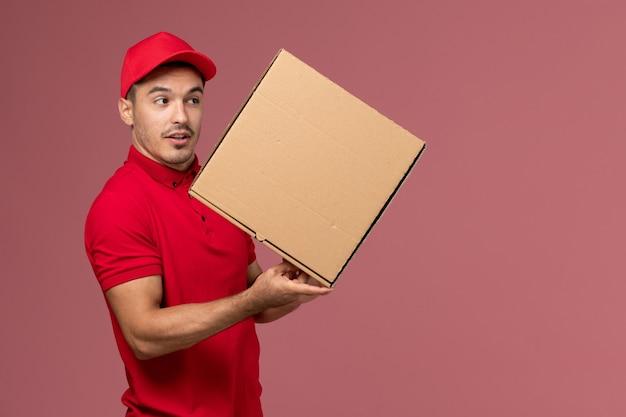 Vue avant du courrier masculin en uniforme rouge et cape tenant la boîte de nourriture sur le travail de travailleur mural rose clair