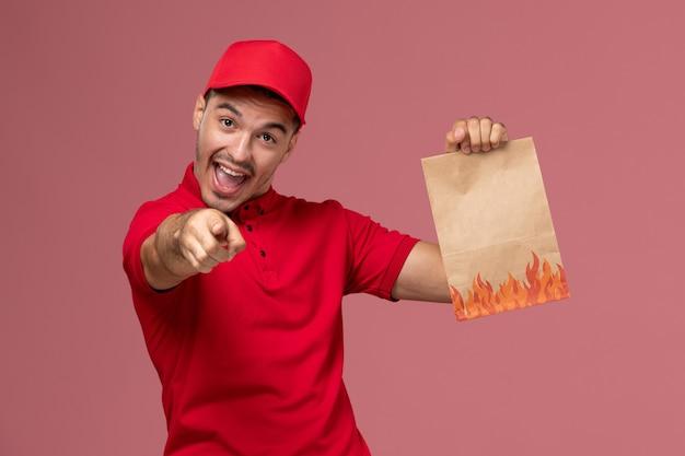 Vue avant du courrier masculin en uniforme rouge et cape tenant le paquet alimentaire papier se réjouissant sur le mur rose
