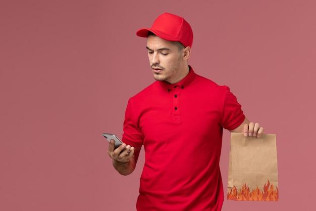 Vue avant du courrier masculin en uniforme rouge et cape tenant le paquet de nourriture et à l'aide de son téléphone sur le mur rose