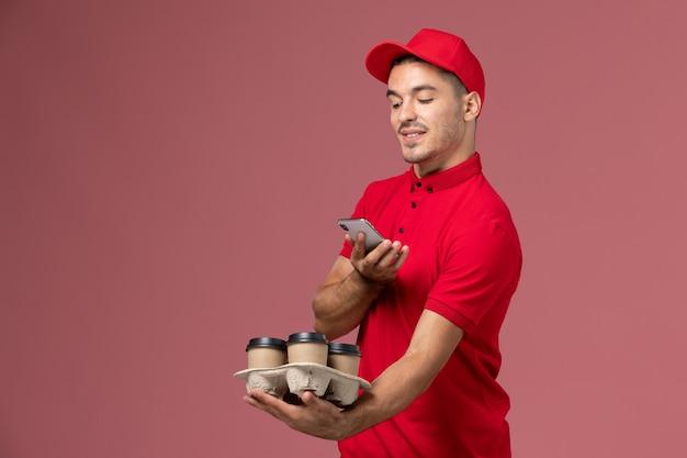 Vue avant du courrier masculin en uniforme rouge et cape tenant des tasses de café de livraison en prenant une photo d'eux sur le mur rose