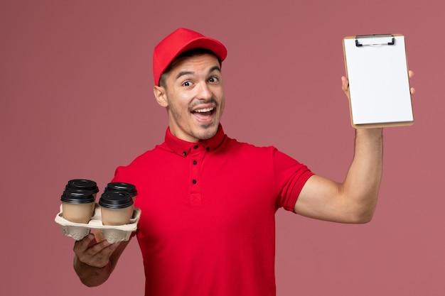 Vue avant du courrier masculin en uniforme rouge se réjouissant et tenant des tasses de café de livraison avec bloc-notes sur bureau rose