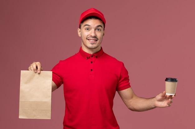Vue avant du courrier masculin en uniforme rouge tenant la tasse de café de livraison et le paquet de nourriture sur le mur rose