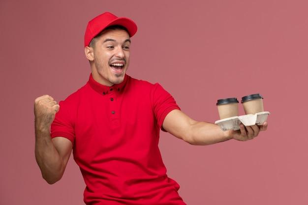 Vue avant du courrier masculin en uniforme rouge tenant des tasses de café de livraison brun se réjouissant sur le mur rose