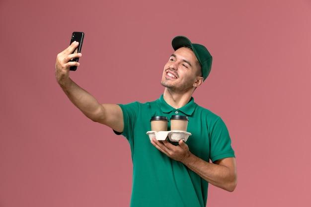 Vue avant du courrier masculin en uniforme vert en prenant une photo avec du café sur le fond rose