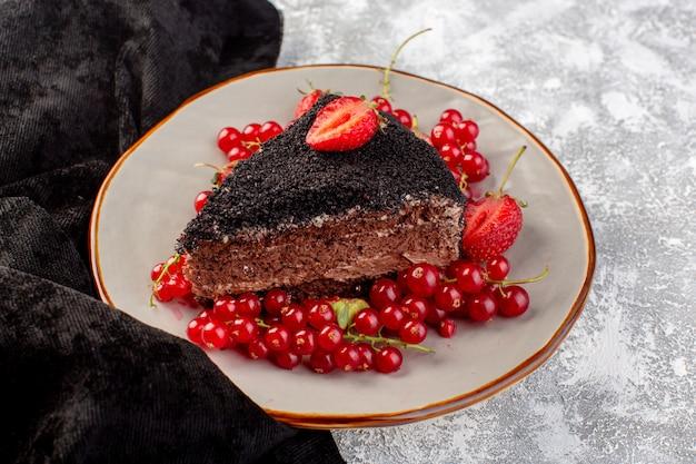 Vue avant du délicieux gâteau au chocolat tranché avec de la crème choco et des canneberges rouges fraîches sur la surface grise