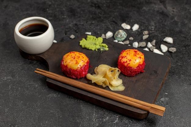 Vue avant du délicieux repas de sushi rouleaux de poisson avec du poisson et du riz avec sauce sur mur gris