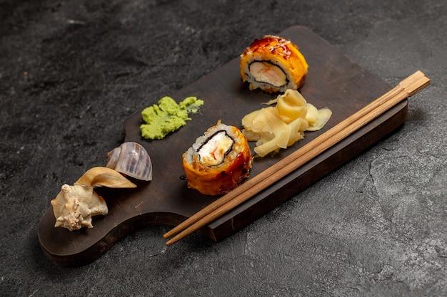 Vue avant du délicieux repas de sushi rouleaux de poisson avec sauce wassabi sur mur gris