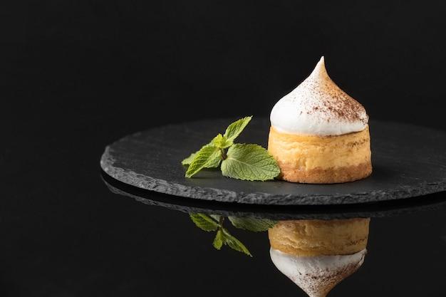Vue avant du dessert avec du cacao en poudre et de la menthe sur ardoise