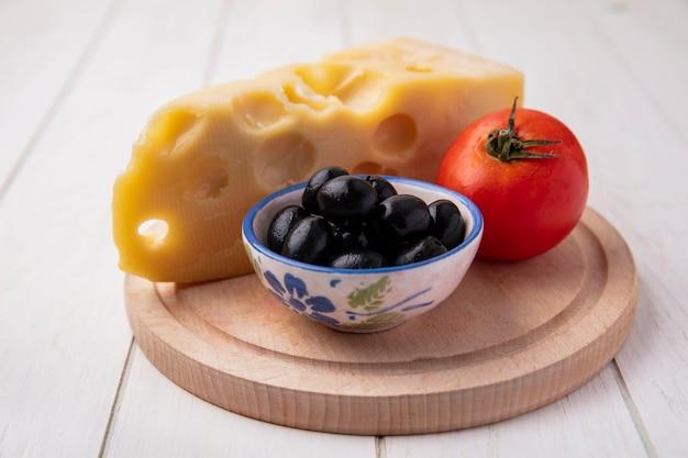 Vue avant du fromage maasdam aux olives et tomates sur un support sur un fond blanc