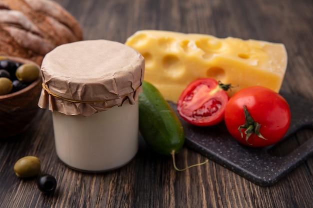 Vue avant du fromage maasdam aux tomates et concombre sur un support avec des olives avec du yaourt sur la table