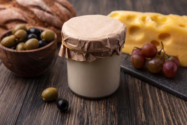 Vue avant du fromage maasdam avec des raisins sur un support et des olives avec du yaourt sur la table