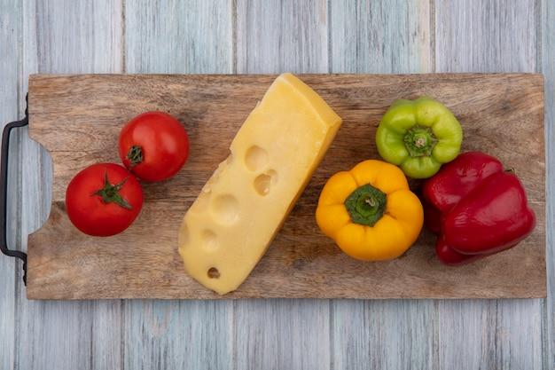 Vue avant du fromage maasdam avec tomates et poivrons sur un support sur un fond gris
