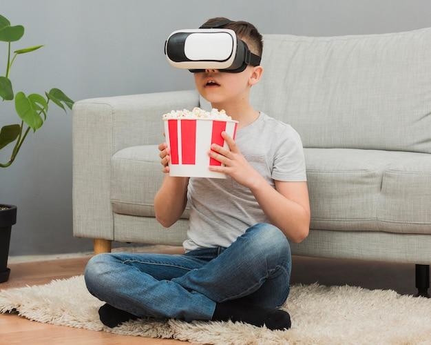 Vue avant du garçon avec du pop-corn en regardant un film à l'aide d'un casque de réalité virtuelle