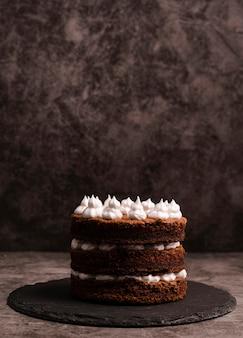 Vue avant du gâteau sur l'ardoise avec copie espace