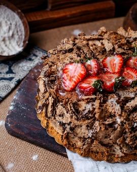 Vue avant du gâteau au chocolat savoureux sucré avec des fraises rouges sur le dessus sur le sol brun