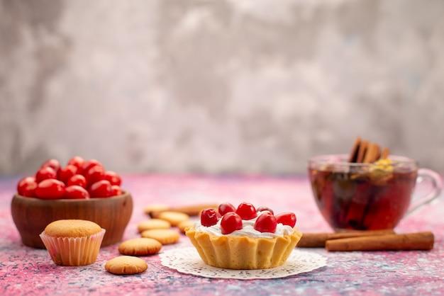 Vue avant du gâteau à la crème avec des canneberges rouges fraîches avec des biscuits à la cannelle et du thé sur le bureau lumineux biscuit thé sucré