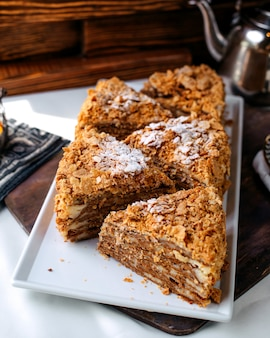 Vue avant du gâteau délicieux délicieux en tranches à l'intérieur de la plaque blanche sur la surface brune