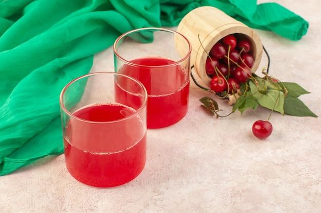 Une vue avant du jus de cerise rouge avec des cerises fraîches sur le bureau rose cocktail boisson couleur fruits