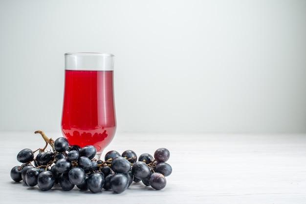 Vue avant du jus rouge avec des raisins sur la surface blanche du jus de cocktail boisson aux fruits