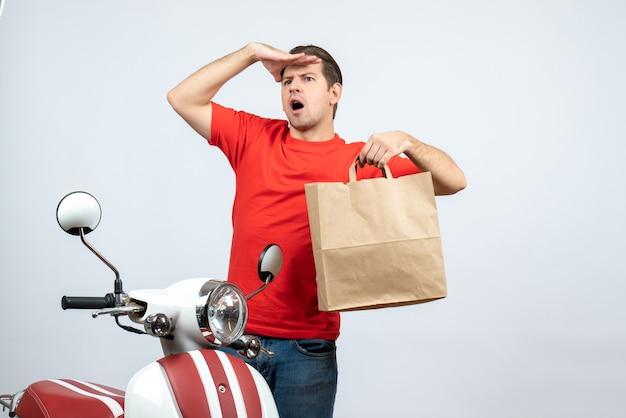 Vue avant du livreur concentré en uniforme rouge debout près de scooter montrant l'ordre sur fond blanc