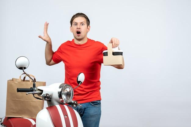 Vue avant du livreur confus en uniforme rouge debout près de scooter montrant l'ordre sur fond blanc