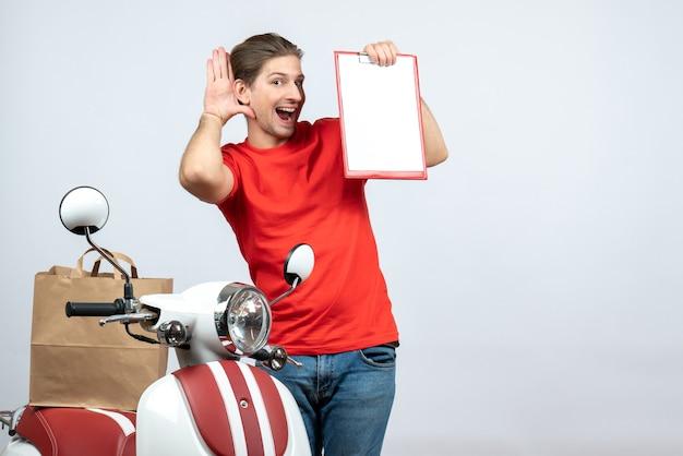 Vue avant du livreur souriant en uniforme rouge debout près de scooter montrant le document à l'écoute des derniers potins sur fond blanc