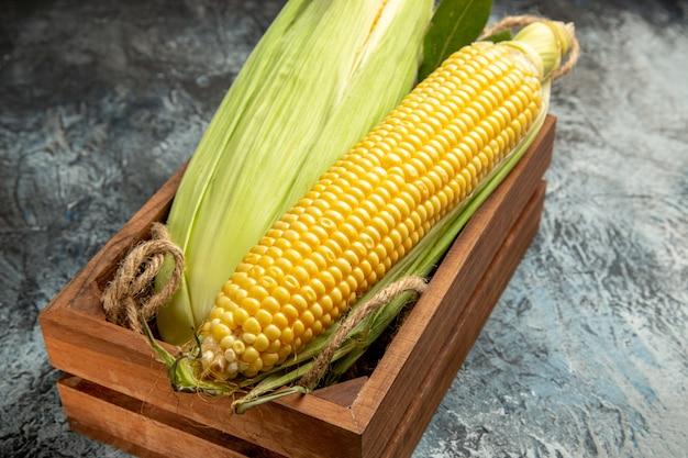 Vue avant du maïs cru frais plante jaune à l'intérieur de la boîte sur fond sombre-clair