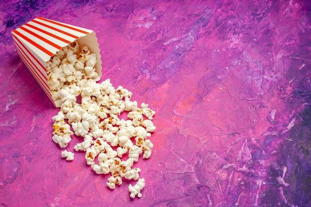 Vue avant du maïs soufflé frais sur une table rose cinéma couleur film de maïs