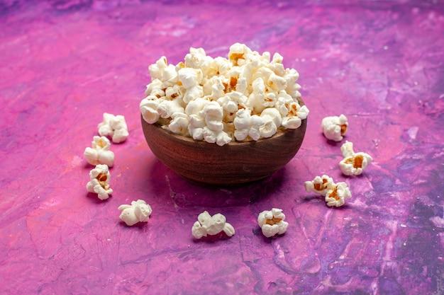 Vue avant du maïs soufflé frais sur table rose cinéma film de maïs