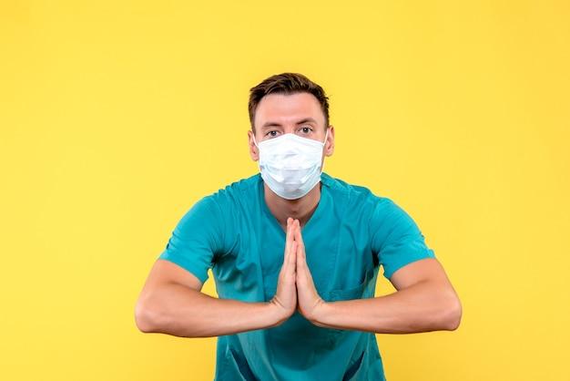 Vue avant du médecin de sexe masculin priant dans un masque stérile sur mur jaune