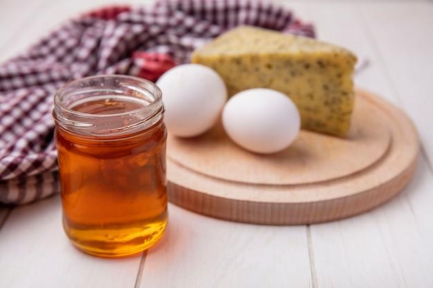 Vue avant du miel dans un pot avec du fromage et des œufs de poule sur un support sur un fond blanc