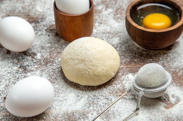 Vue avant du morceau de pâte crue avec des oeufs et de la farine sur la pâte de repas de table pâte crue