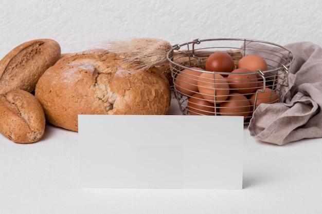 Vue avant du pain frais avec des œufs et du papier vierge