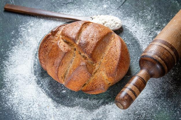 Vue avant du pain noir avec de la farine
