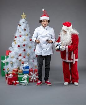 Vue avant du père noël avec cuisinier masculin autour de cadeaux de noël sur mur gris