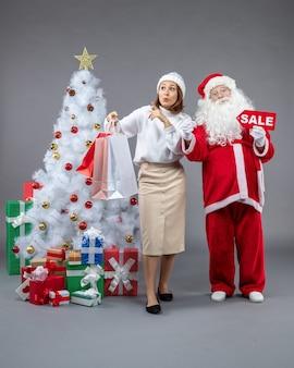 Vue avant du père noël avec jeune femme autour de l'arbre de noël et présente sur le sol gris noël froid vacances de neige du nouvel an
