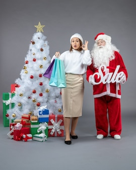 Vue avant du père noël avec jeune femme autour de cadeaux sur le fond gris